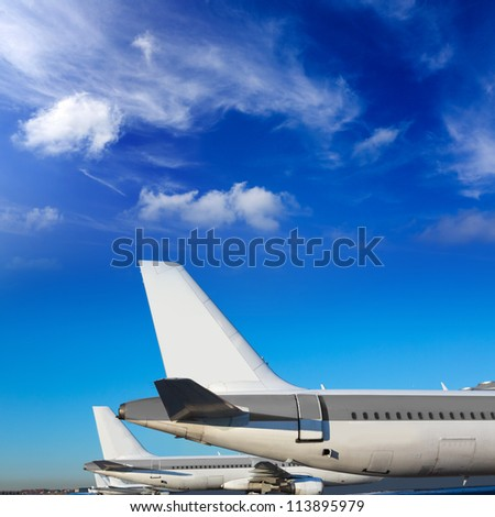 Airplanes in a row under blue sunny sky - stock photo