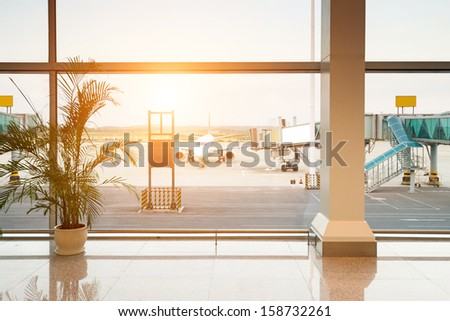 Airport, A huge viewing glass facade with a passenger aircraft behind it. - stock photo