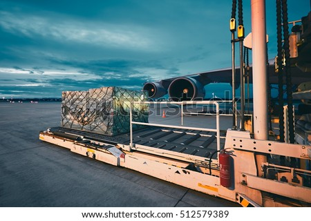 Airport at the dusk. Loading of cargo to the freight aircraft.