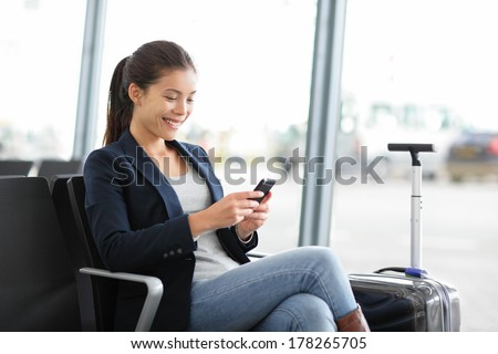 Airport business woman on smart phone at gate waiting in terminal. Air travel concept with young casual businesswoman sitting with hand luggage suitcase. Beautiful young mixed race female professional - stock photo