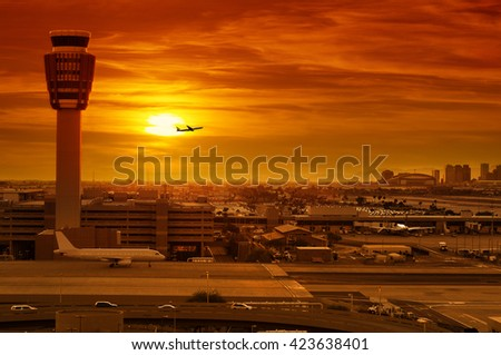 airport control tower and airplane taking off at sunset - stock photo