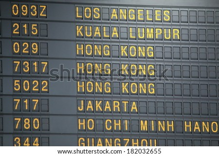 Airport departure board showing flight information  - stock photo