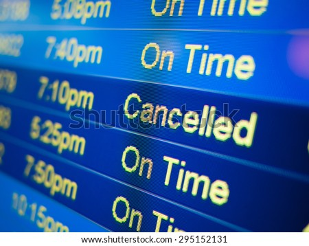 Airport flight cancelled. Airport arrival and departure monitor sign showing on-time and cancelled flight status - stock photo