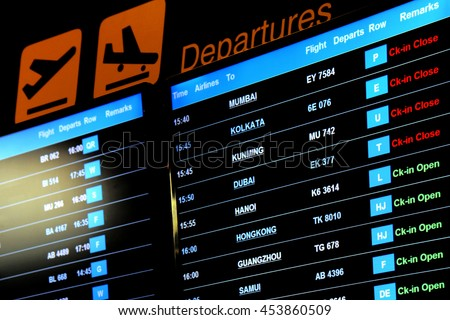 Airport flight information on a large screen international departure board - stock photo