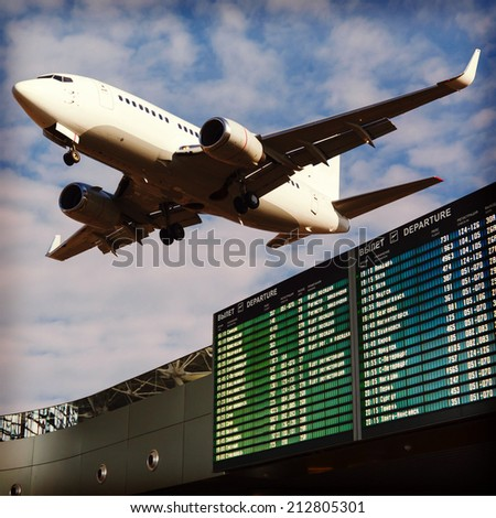 Airport flight information with the list of flights in the sky and the plane - stock photo