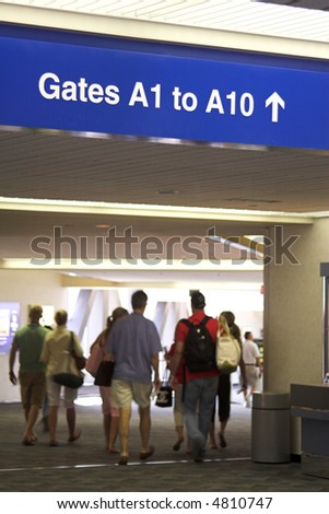 Airport gate sign and travelers heading to the boarding gates. - stock photo