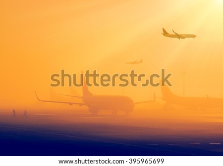 Airport in a foggy weather - silhouettes of airplanes early in the morning. Aircrafts in a fog, international airport at sunrise. Air travel - passenger and commercial transportation. - stock photo