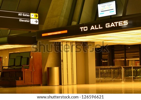 Airport interior with gates direction sign at night - stock photo