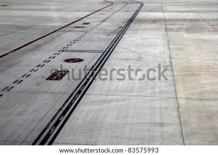 airport landing runway road with painted black horizontal signals - stock photo