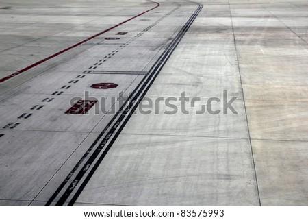 airport landing runway road with painted black horizontal signals - stock photo