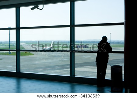 Airport lounge or waiting area with business man standing looking outside of window towards control tower - stock photo