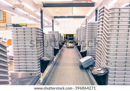 Airport luggage conveyor belt at international departures gate - Modern baggage belt transports system - Traveler suitcases on carries to the airplane - Focus on the golden bag at the center - stock photo