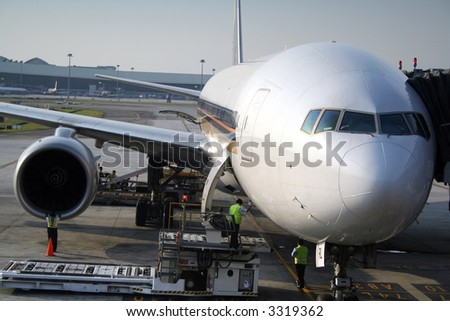 Airport maintenance crew checking and servicing a passenger plane during transit. - stock photo