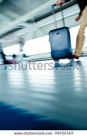 Airport rush: people with their suitcases walking along a corridor (motion blurred image; color toned image) - stock photo