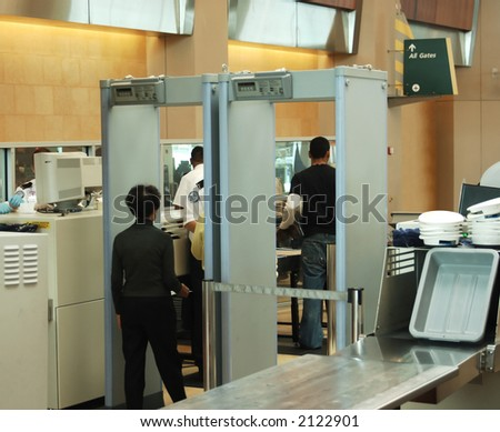 airport security check with passenger walking through metal detector - stock photo