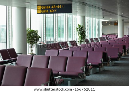 Airport terminal departure lounge with gate sign and seating - stock photo