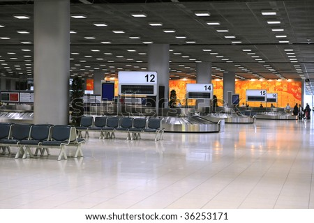 Airport terminal with baggage carousels for travelers - stock photo