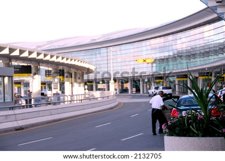 Airport terminal with cars outside - stock photo