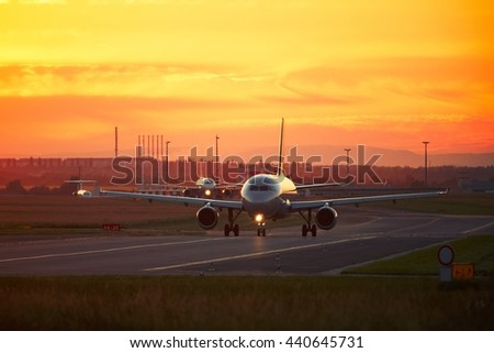 Airport traffic at the golden sunset. Airplanes are taxiing to the runway for take off. - stock photo