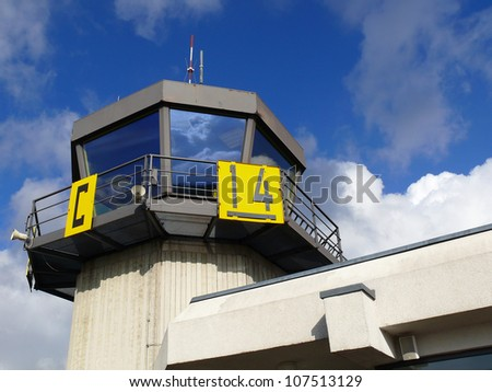 Airport traffic control tower with cloudy sky on background and strong reflection of sky in windows - stock photo