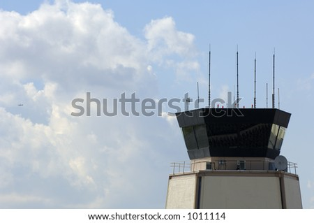Airport traffic control tower with small airplane taking off - stock photo