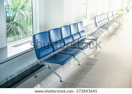 Airport waiting area with rows of blue seats. Background for topics of travel and business. - stock photo