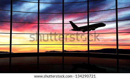 Airport window with airplane flying at sunset - stock photo