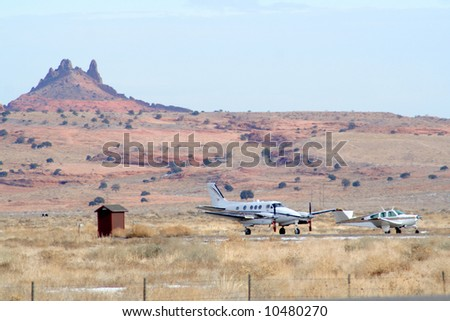 Airport with planes by Colorful red rock outcropping in monument valley arizona - stock photo