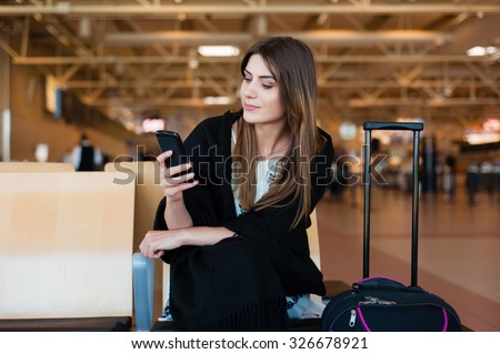 Airport Young female passenger on smart phone at gate waiting in terminal while waiting for her flight. Air travel concept with young casual woman sitting with hand luggage suitcase. - stock photo