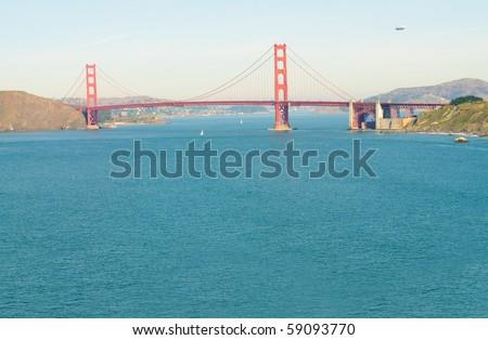 Airship or blimp cruising over San Francisco and the Golden Gate Bridge - stock photo