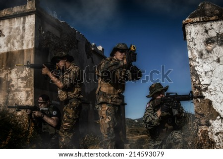 Airsoft group team in daytime action walking in terrain recognition  with a gritty and grunge effect.  - stock photo