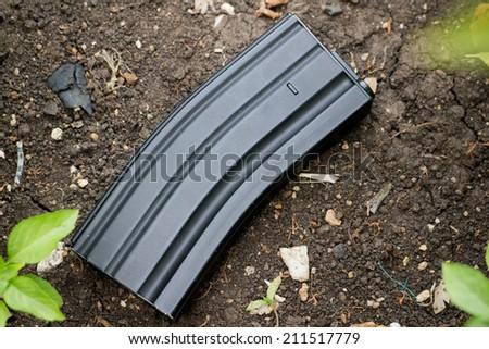 Airsoft gun magazine on the ground  - stock photo