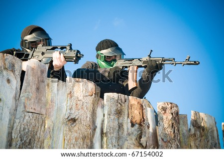 Airsoft players with protective masks shooting - stock photo