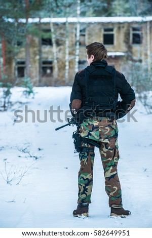 airsoft sport player  aiming pistol ,black armor and machine gun