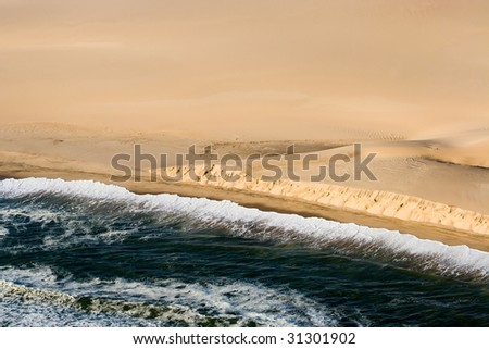 airview of waves rolling over the beach - stock photo