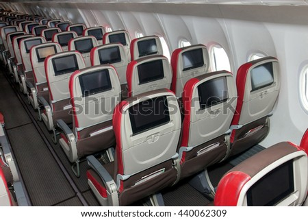 Aisle seats on empty planes. View of the rear part of seat with monitors inside aircraft without people. Empty board of airliner.
