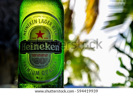 Aitutaki, Cook Islands - January 23, 2012: Close up detail of a Heineken beer bottle, illuminated by the evening sun. In the background there are palm trees on the beach of Aitutaki, Cook Islands.