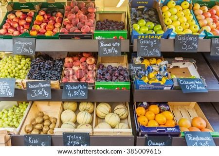AIX-EN-PROVENCE, FRANCE - AUGUST 14, 2015: Fruit stand at the street market in France selling apples, kiwi, lemon, peach, grapes, plums, melons, oranges - with prices in Euroes written on the labels