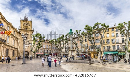 AIX EN PROVENCE, FRANCE - JULY 8, 2015: people enjoy sitting at the central place in Aix en  provence at town hall square. The townhall was built in the 17th century. - stock photo