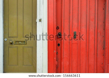 Ajacent green and red wooden front doors of English cottages