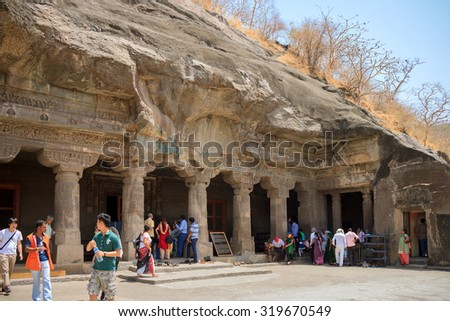 AJANTA, MAHARASHTRA, INDIA - 24 APR: Total activity of tourists near the monolithic caves at Ajanta, Maharashtra, India - 24 APR 2015. Tourists view carved ancient caves, sometimes called Indian Petra - stock photo