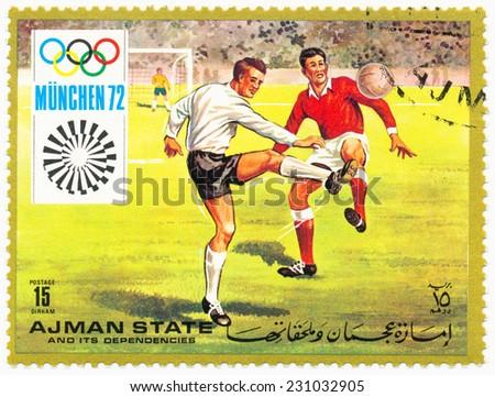 AJMAN - CIRCA 1972: A stamp printed in Ajman shows footballers, Olympics in Munich, circa 1972 - stock photo