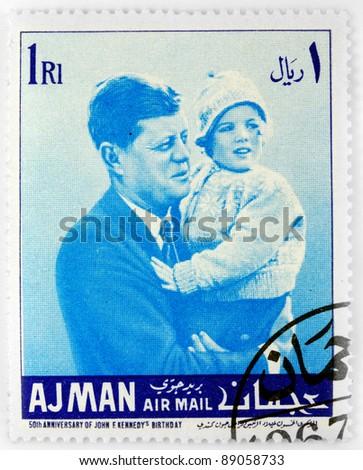 AJMAN - CIRCA 1967: A stamp printed in Ajman shows John F. Kennedy with his daughter Caroline Kennedy , circa 1967 - stock photo