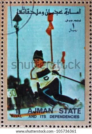 AJMAN - CIRCA 1973: a stamp printed in the Ajman shows Slalom, Alpine Skiing, Winter Olympics, circa 1973 - stock photo