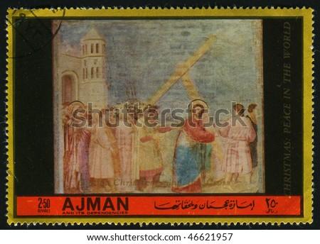 AJMAN - CIRCA 1985: Jesus Christ bears a cross, circa 1985. - stock photo