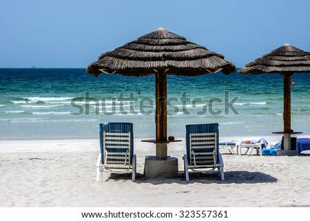 AJMAN, UNITED ARAB EMIRATES - SEPTEMBER 5, 2015: Beautiful beach Ajman Kempinski Resort - luxurious 5-star hotel nestled near turquoise waters of Arabian Gulf. Resort has 166 sea view rooms, 14 suites - stock photo