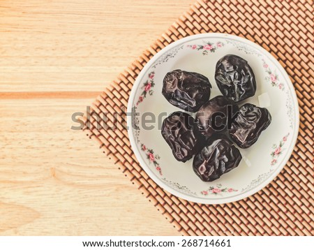 Ajwa Dates fruit on wooden table (Ajwa is a soft dry variety of date fruit from Saudi Arabia. It is cultivated at the city of Madinah) - stock photo