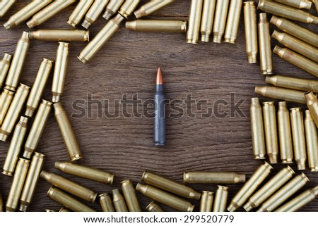 Ak-47 cartridges on wooden table close-up. - stock photo