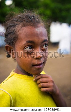AKSUM, ETHIOPIA - SEP 27, 2011: Portrait of an unidentified Ethiopian cute girl in a yellow shirt in Ethiopia, Sep.27, 2011. Children in Ethiopia suffer of poverty due to the unstable situation