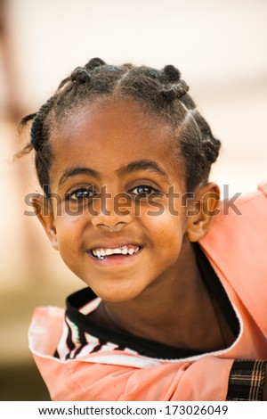 AKSUM, ETHIOPIA - SEP 24, 2011: Unidentified Ethiopian cute little girl with pigtails smiles in Ethiopia, Sep.24, 2011. Children in Ethiopia suffer of poverty due to the unstable situation